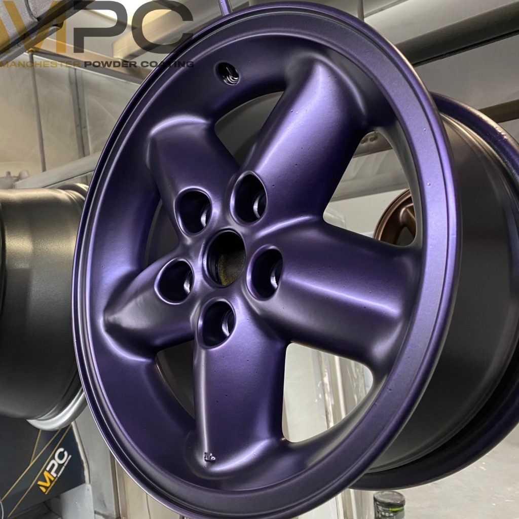 An image of a car alloy with a powder coating in a satin purple colour
